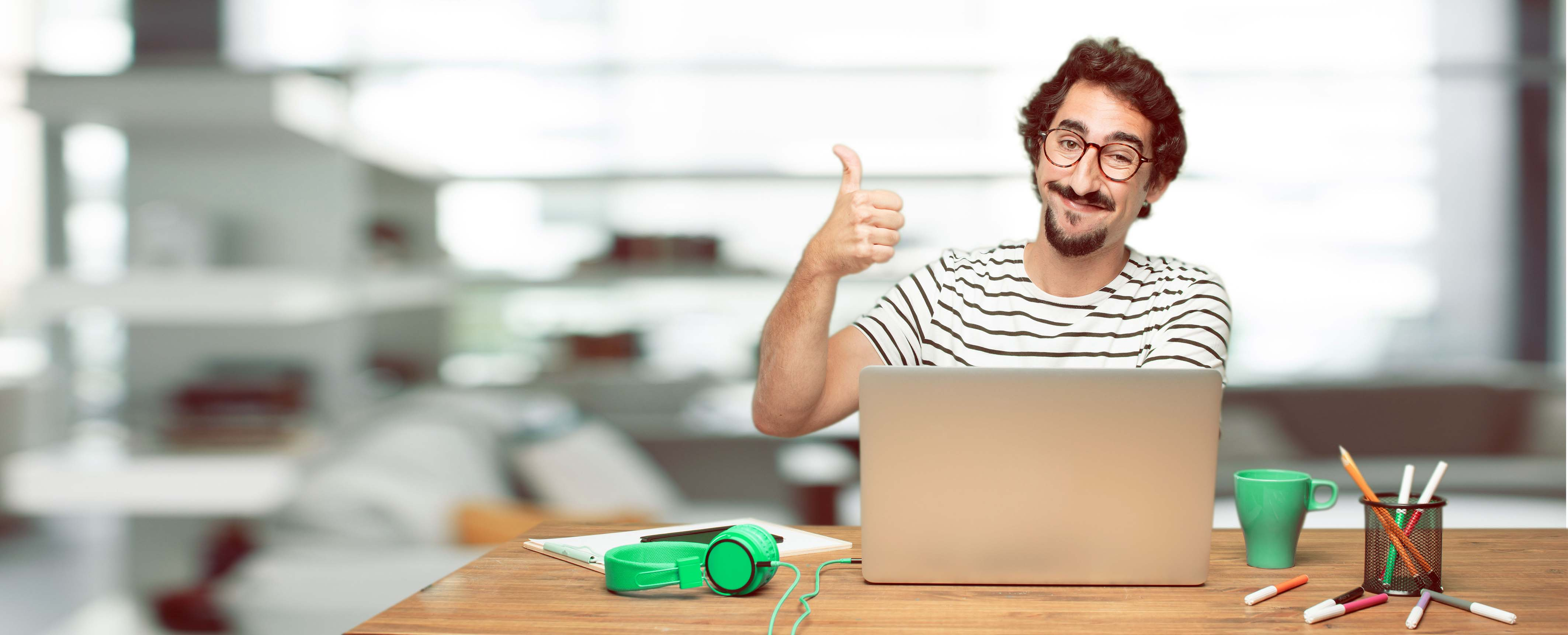 Hombre joven con un computador haciendo visto bueno con su pulgar arriba