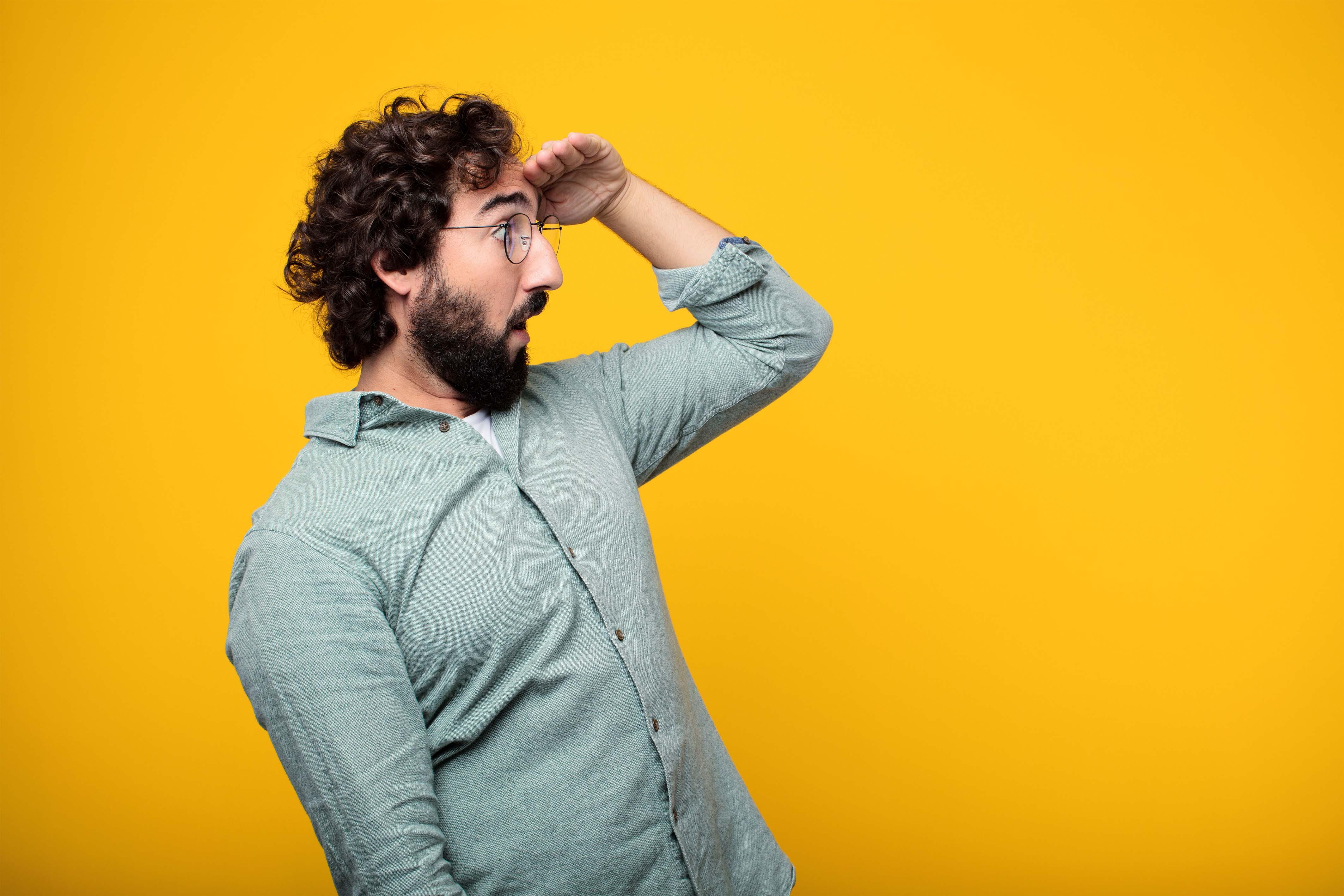 Hombre inclinado hacia su izquierda mirando el horizonte en fondo amarillo